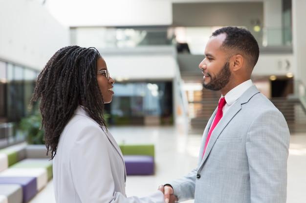Счастливые уверенные деловые люди заканчивают свою встречу
