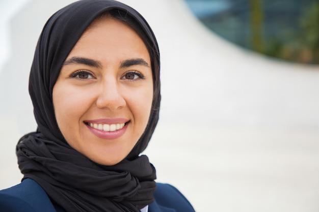 幸せな自信を持ってイスラム教徒のビジネス女性が外でポーズ