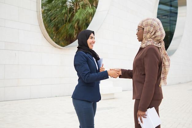 Счастливые мусульманские деловые партнеры приветствуют друг друга