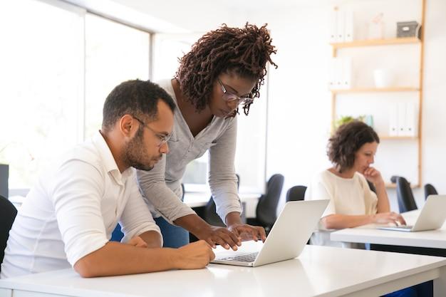 Инструктор помогает стажеру начать работать на ноутбуке