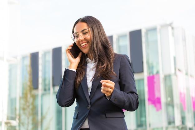 Радостная латинская деловая женщина звонит на сотовый