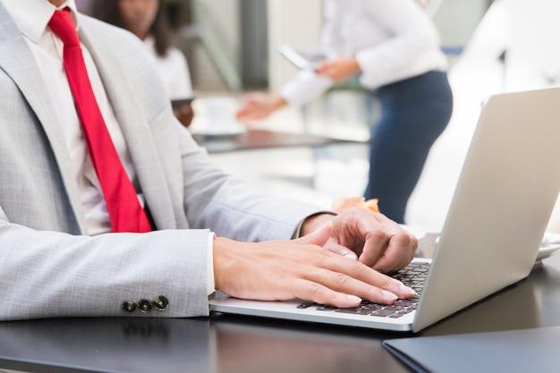 Мужской исполнитель, используя ноутбук в кафе