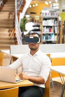Пользователь библиотеки мужского пола, носящий наушники виртуальной реальности