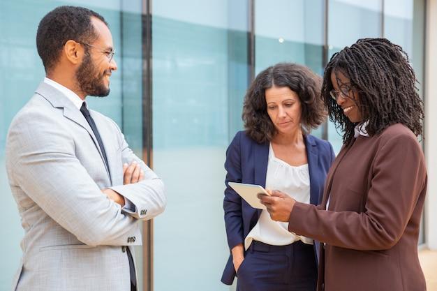 多民族のビジネスチームがプロジェクトデータを見て議論