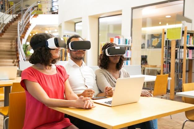 Многорасовая команда взрослых студентов, носящих наушники виртуальной реальности