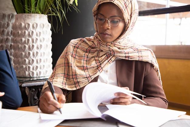 Мусульманская деловая женщина сканирует контракт