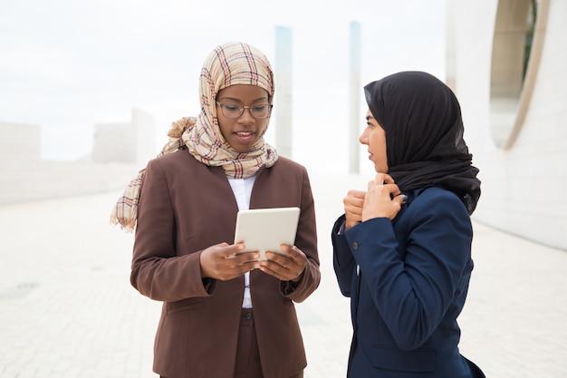 Мусульманская бизнес-леди советуя с коллегой с таблеткой