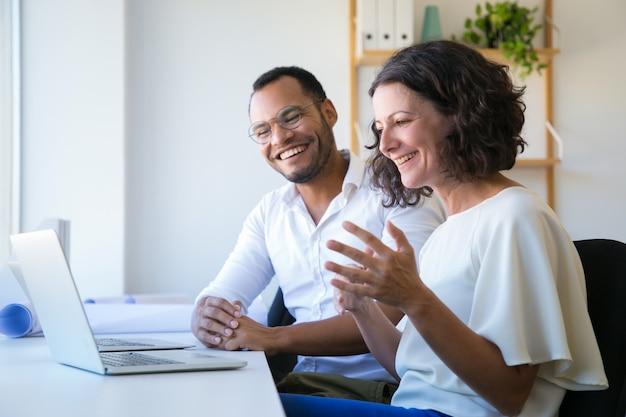 Веселые коллеги используют ноутбук для видеозвонка
