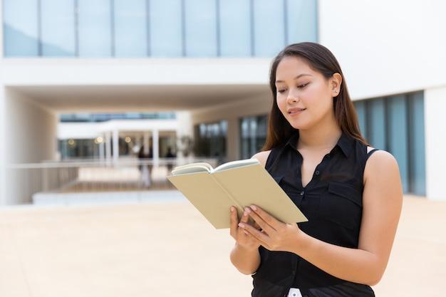 Веселый улыбающийся студентка, чтение учебника