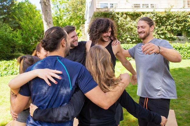 Веселые молодые люди обнимаются на открытом воздухе