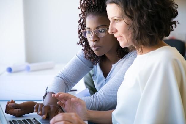 Профессиональная женщина, показывающая особенности программного обеспечения коллеге