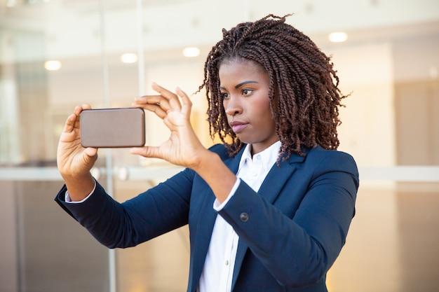 プロの女性が携帯電話で写真を撮る