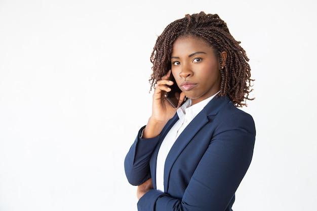 Серьезный уверенный бизнес-лидер говорит по мобильному телефону