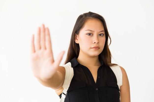 Строгая серьезная девочка-подросток делает жест рукой стоп