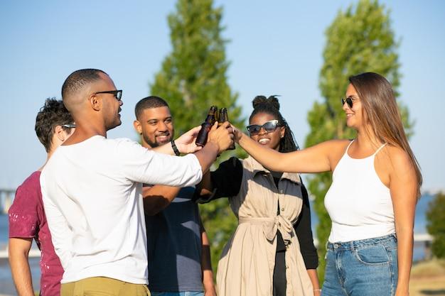 Счастливые многонациональные друзья наслаждаются пивной вечеринкой в парке