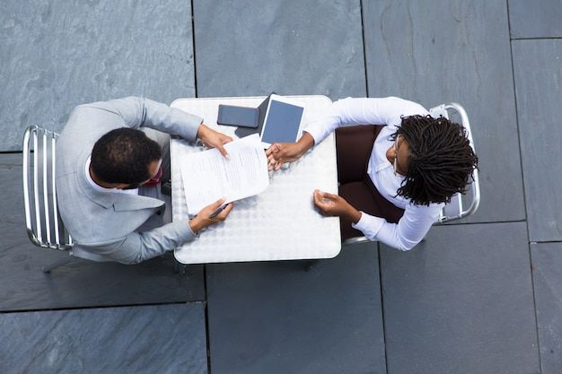 Афро-американская деловая женщина передает документы коллеге