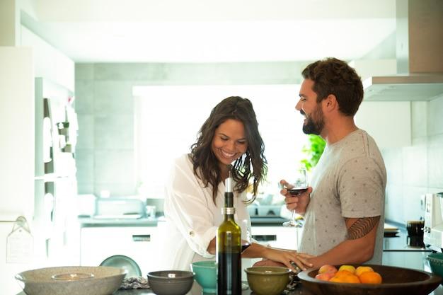 陽気なカップルがワインを飲む