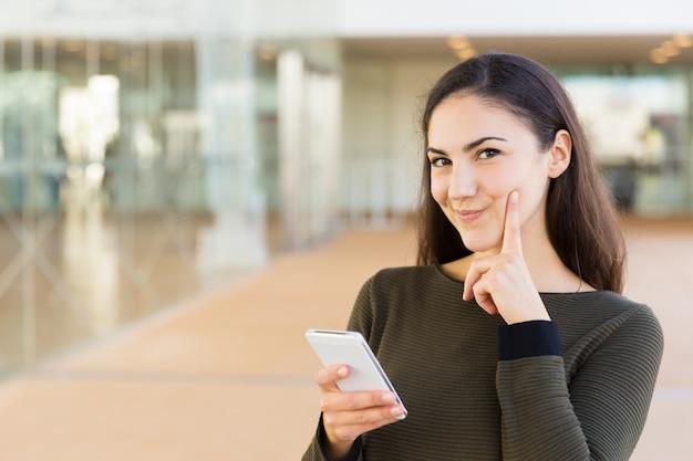 Веселая задумчивая латинская женщина с мобильным телефоном