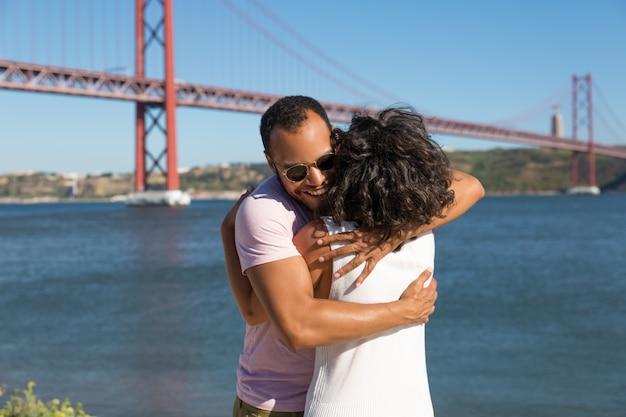 川の近くを抱いて陽気な若いカップル