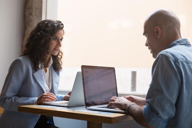 Два коллеги используют ноутбуки во время перерыва в кафе