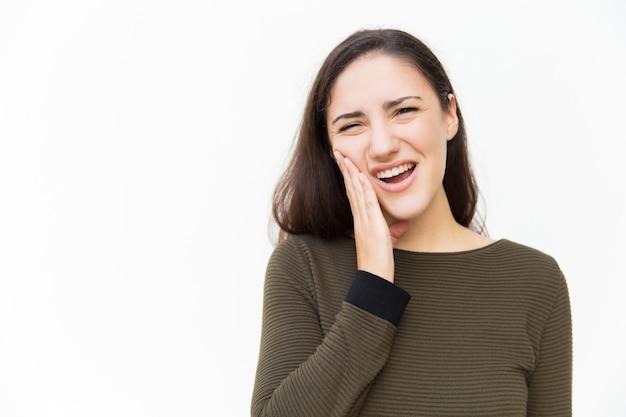 Расстроенная женщина с болью гримасой страдает от зубной боли