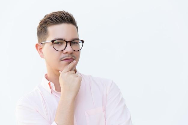 Крупным планом задумчивый серьезный парень в очки, касаясь подбородка