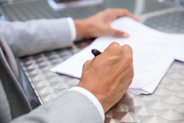 Взгляд крупного плана бумаги подписания мужской руки