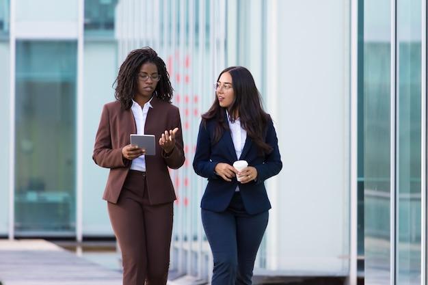 Уверенно деловая женщина гуляет с планшетом