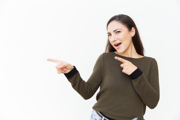 Возбужденная веселая красивая женщина, указывая указательными пальцами