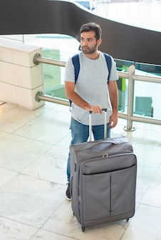 空港で荷物を持って焦点を当てたひげを生やした旅行者