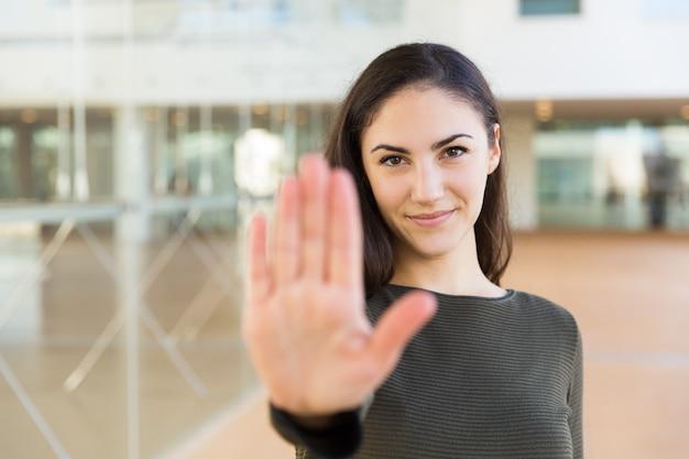 Дружелюбная уверенно красивая женщина, делая жест рукой стоп