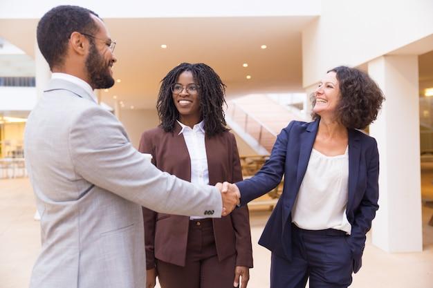 Счастливые деловые партнеры приветствуют друг друга