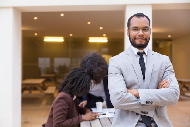 Счастливый уверенно мужской профессиональный позирует со сложенными руками