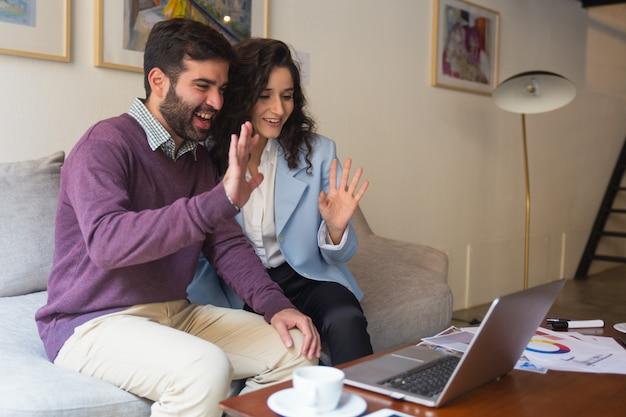 コンピューターの画面でこんにちはを振って幸せなカップル