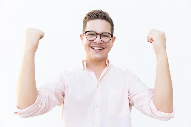 Счастливый возбужденный парень в очках празднует успех
