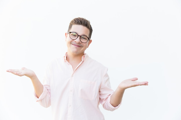 Счастливый дружелюбный парень в очках пожимает плечами