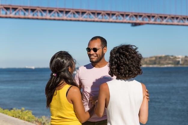 Счастливые друзья стоят возле реки