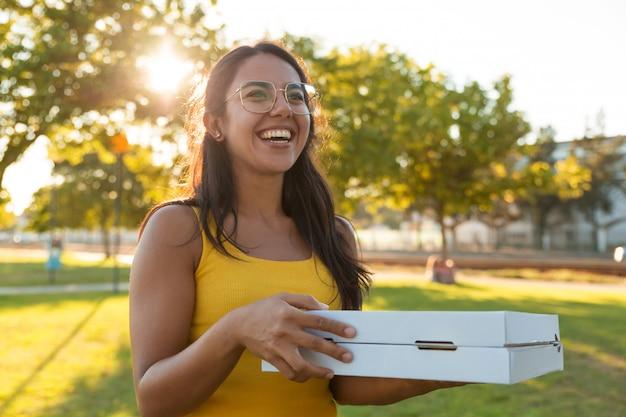 ピクニックのためのピザを運ぶ幸せなうれしそうな若い女性