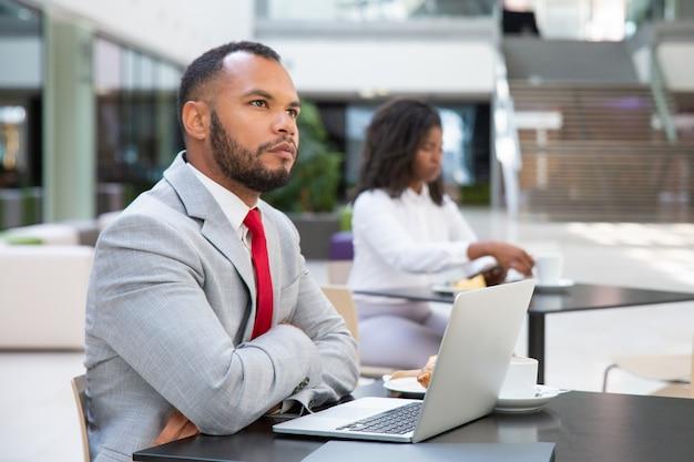 Задумчивый бизнесмен с ноутбуком, продумывая стратегию запуска