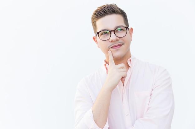 Задумчивый предприниматель касается подбородка и смотрит в сторону