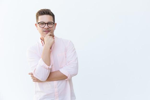 Задумчивый парень в очках, касаясь подбородка и глядя