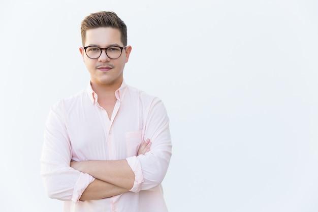 Положительный уверенный предприниматель позирует с сложив