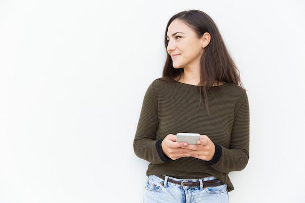 Положительная задумчивая женщина держа мобильный телефон
