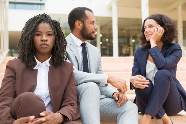 階段に座っている深刻なアフリカ系アメリカ人ビジネス女性