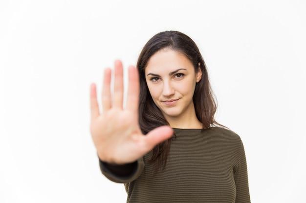 Серьезная уверенно красивая женщина делает жест рукой стоп
