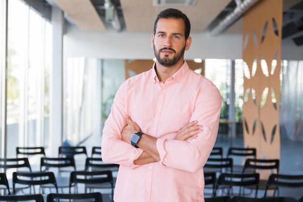 Серьезный уверенный бизнес-тренер позирует со сложенными руками