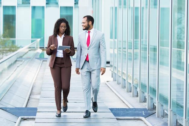 Улыбающийся афро-американский мужчина слушает коллегу