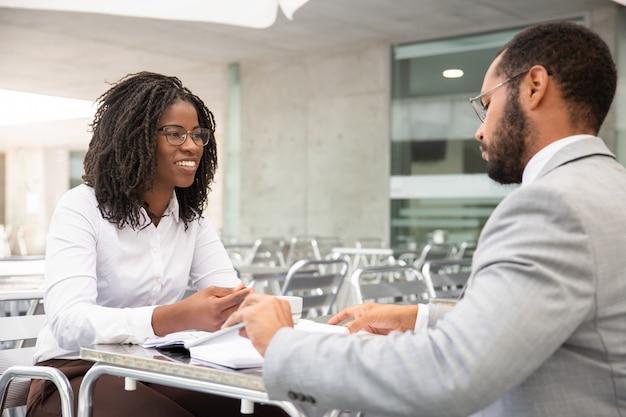 同僚を見て眼鏡で笑顔のアフリカ系アメリカ人女性