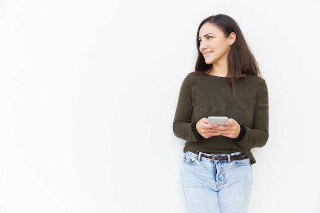 Усмехаясь сфокусированная женщина держа мобильный телефон и смотря прочь