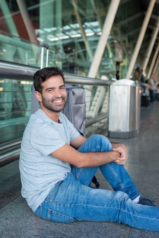 空港の床に座っている笑顔のヒスパニック系の男